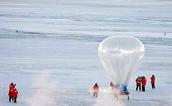 Large balloon flies above snowfield.