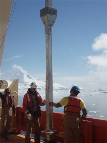 NBP crew handles coring instrument on ship.
