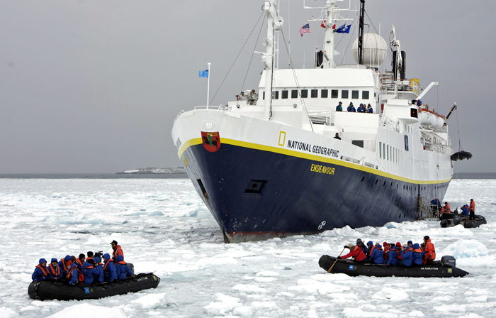 Tourists board Zodiacs from cruise ship.