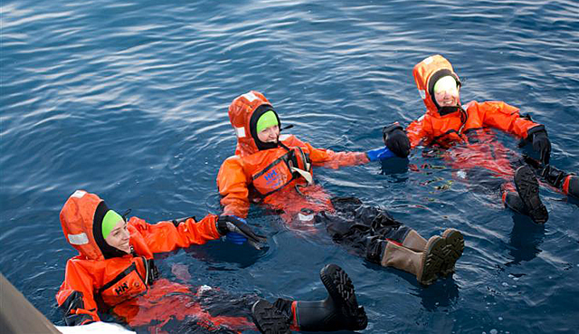 People in orange suits float in water.