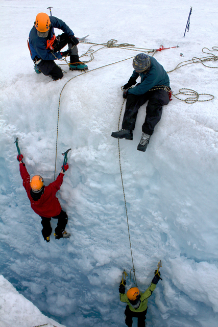People belay others down a crevasse.