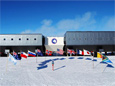 Flags fly at the ceremonial South Pole in front of the Elevated Station in honor of the 12 original signatory nations of the Antarctic Treaty. Credit: Dwight Bohnet