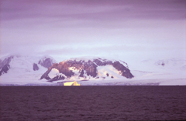Iceberg in front of mountainous island.