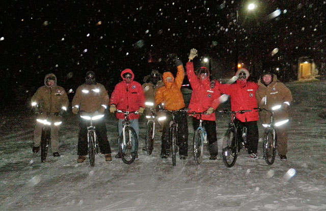 People bike at night in cold weather.
