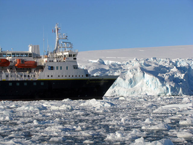 Ship moves through icy sea.