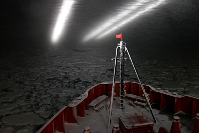 A ship pushes through ice at night.
