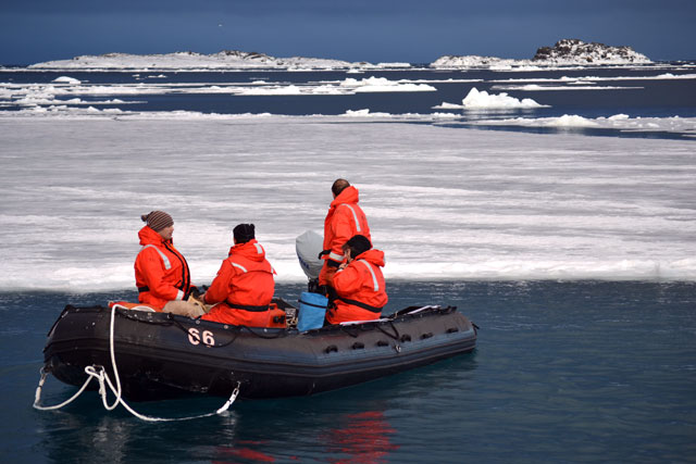 Boat with people surrounded by ice.