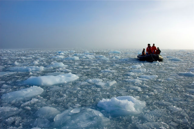 People on a boat going through ice.