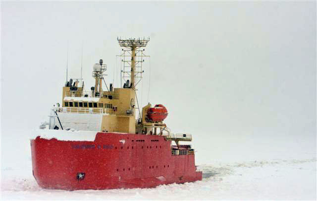 Ship sails in snowy conditions.