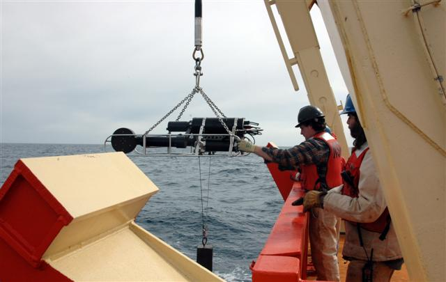 People deploy an instrument off stern of a ship.