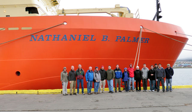 Group of people stands in front of ship.