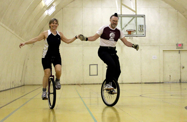 Two people on unicycles in a gym.
