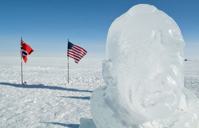 Head made out of ice in front of flags.