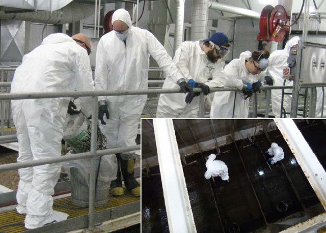 People in white smocks clean facility.