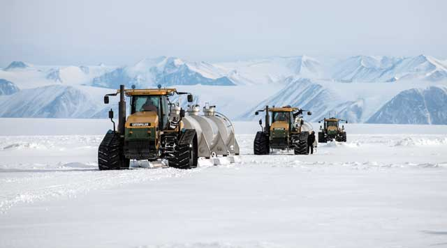 Line of tractors pull tanks on sleds.