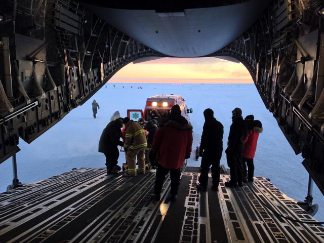 People inside a plane await a patient offload.