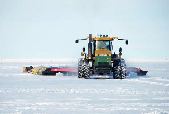 Tractors pulls a sled across snow.