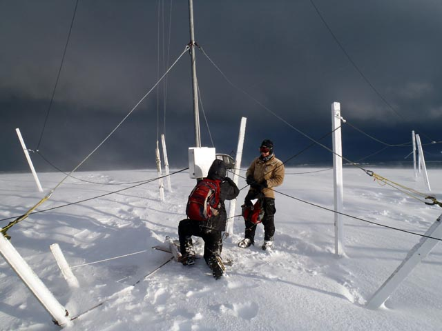People work on an antenna in the cold.