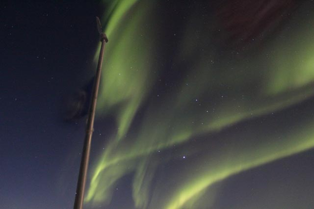 An aurora shines in the night sky.