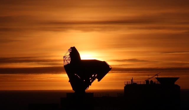 Telescope backlit by setting sun.
