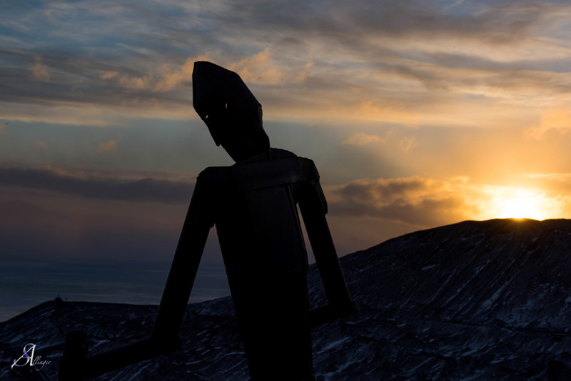 The setting sun silhouettes McMurdo Station's skiing man statue