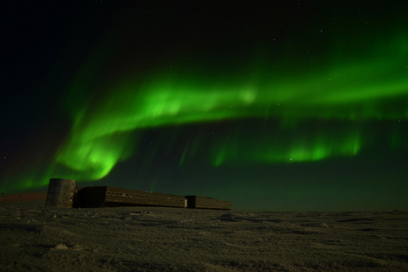 A beautiful green aurora dominates the night sky over the South Pole Station