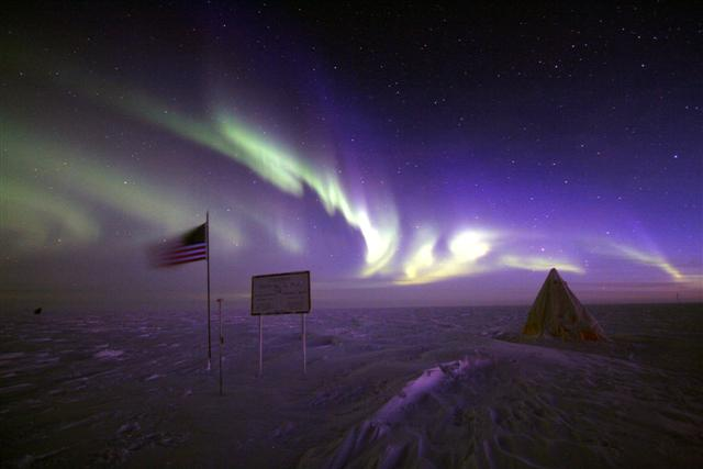 An aurora illuminates the geographic pole.
