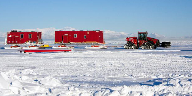 Traverse tractors pulls two buildings on sleds.