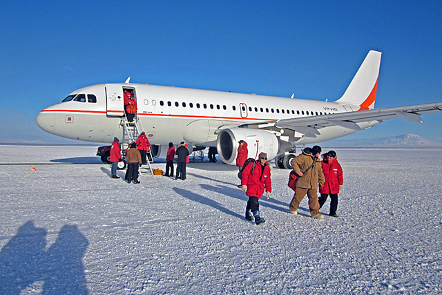 People exit plane sitting on ice.