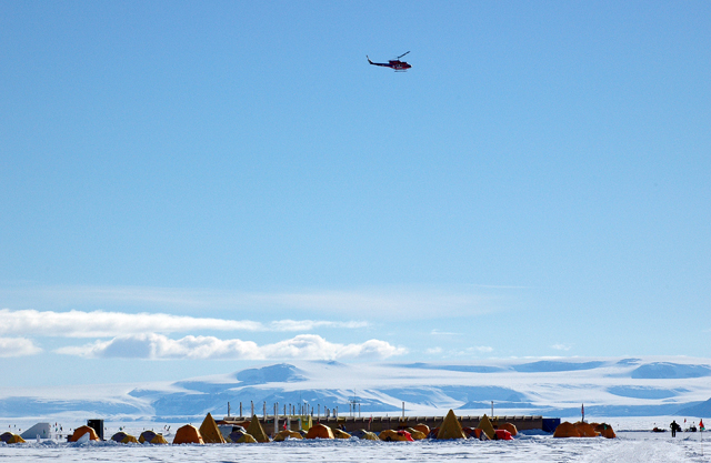 Helicopter flies over camp.