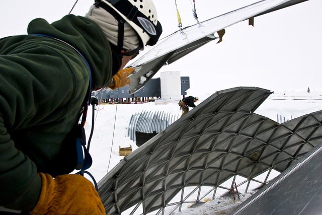 A worker helps guide a section of wall away from the dome.