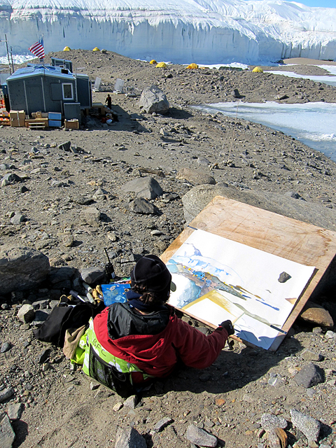Woman drawing glacier and buildings.