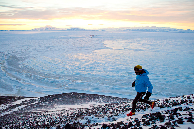 Person runs on trail above sea ice.