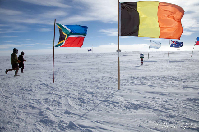 People run near flags on snow.
