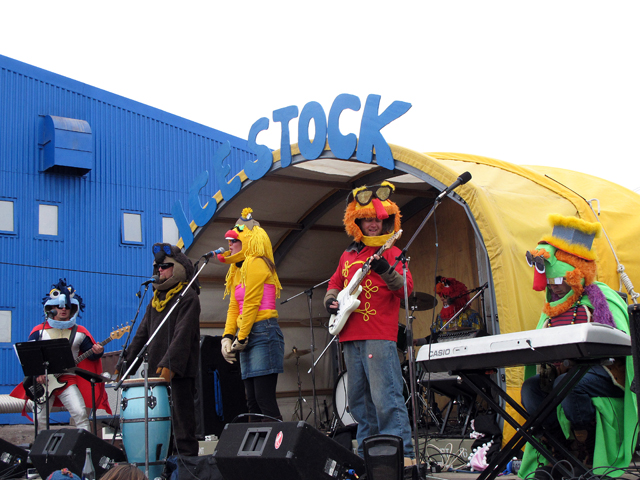 Band dressed in costumes on a stage.