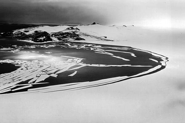 Black and white photo of ocean and ice.