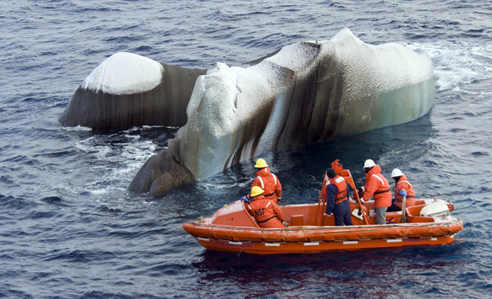 Scientists examine chunk of ice from a small boat.