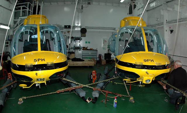 Two helicopters in a ship hangar.
