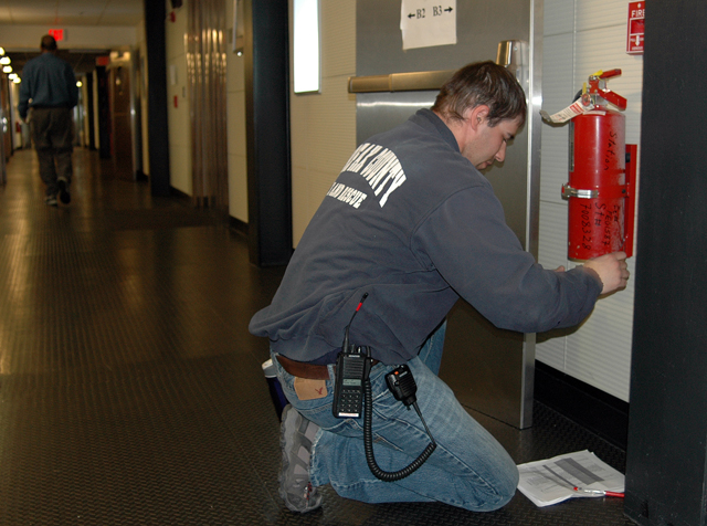 Person inspects fire extinguisher.