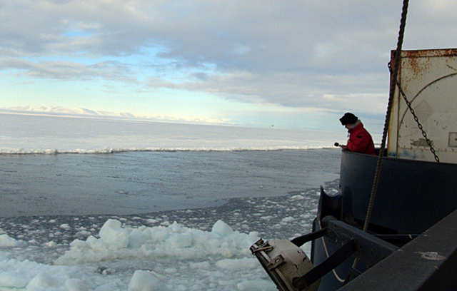 Man on ship in ice and water.