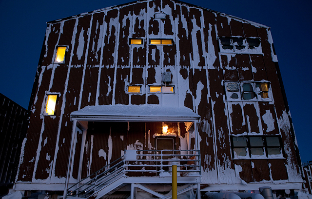 A dorm bulding covered in ice and snow.