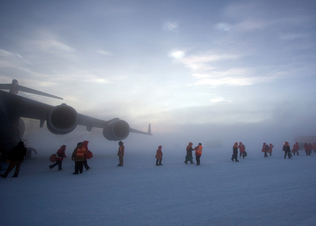A line of passengers leaves the C-17.