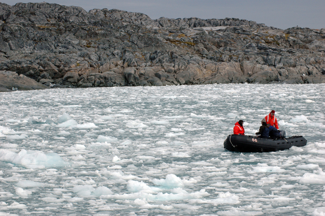 Dive boat pushes through brash ice in Hero Inlet.
