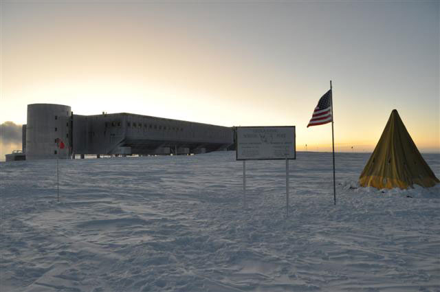 Large building on snow with tent, sign and flag in foreground.