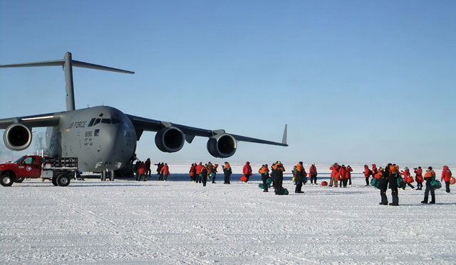 People exit a large aircraft sitting on ice.