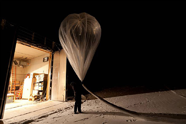 Person prepares to launch balloon at night.