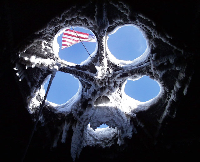 American flag seen through hole in a roof.