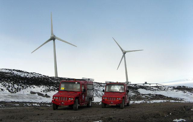 Two cars in front of turbines.