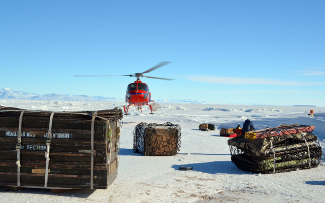 A helicoper lands in front of bundles on pallets.