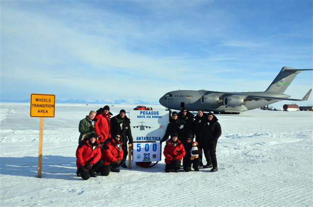 People pose in front of plane on ice.